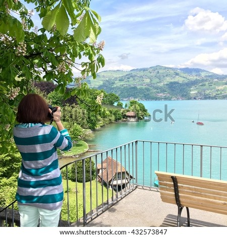 Woman taking picture of Thun (Thunersee) lake in Switzerland. - stock photo