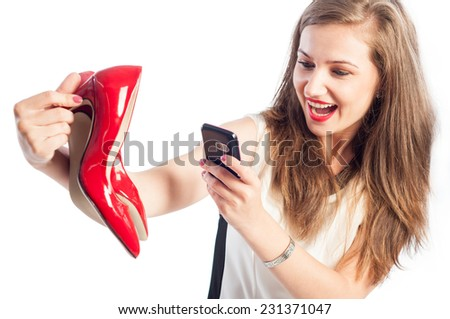 Woman taking pictures with red shoes using her smartphone - stock photo