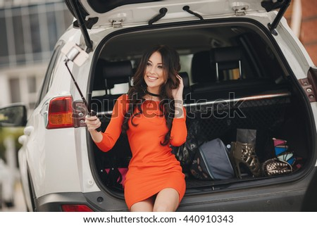 woman taking selfie in back trunk of car before leaving for vacations. girl taking self portraits sitting in back trunk of car with suitcases. Vacation, trip concept. Road travel. - stock photo