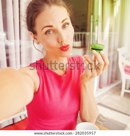 "woman taking selfie with macaroon (""instagram"" style filter and crop applied) - stock photo"