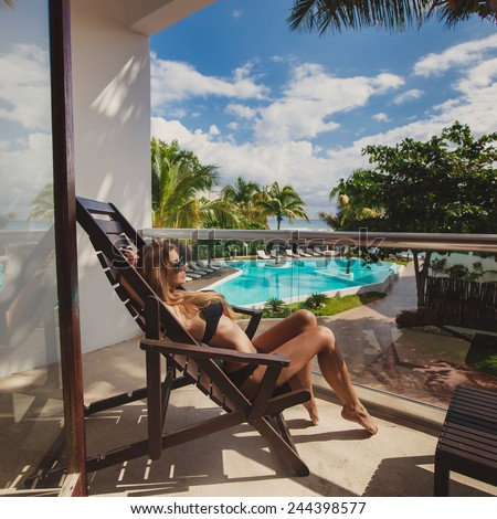 woman taking sunbath near swimming pool. beautiful woman on a tropical beach on a chaise lounge. Woman lying in a deck-chair in a hotel and enjoying sun. Young beautiful woman outdoors on the sunbed - stock photo