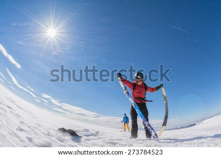 woman taking the skins off of her touring skis on a plateau in the wind - stock photo