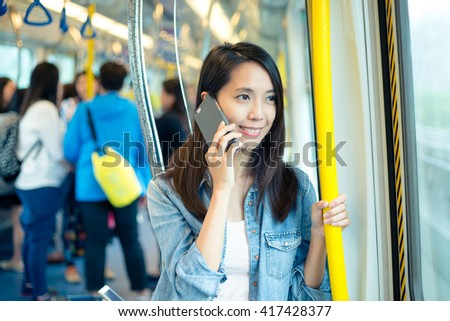 Woman talk to cellphone inside train compartment - stock photo