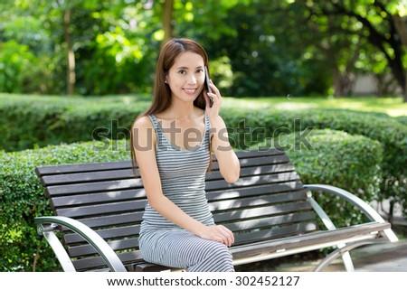 Woman talk to phone at park - stock photo