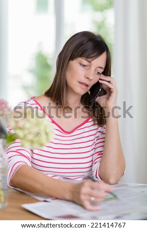 Woman talking on a telephone following up on an advertisement in the newspaper spread out on the table in front of her - stock photo