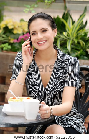 woman talking on cell phone in outdoor cafe - stock photo