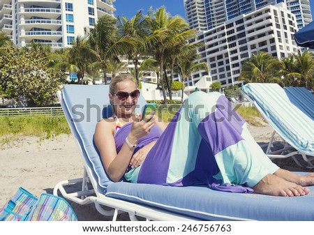 Woman talking on her cell phone while lounging on the beach - stock photo