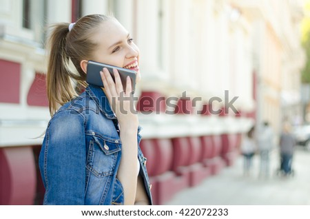 Woman talking on mobile phone in the street - stock photo