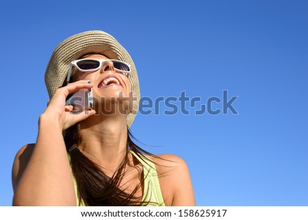 Woman talking on the cell phone and smiling against blue copy space sky. Young girl on happy call laughing and having fun. - stock photo