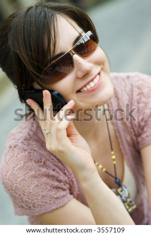 Woman talking on the phone and getting good news - stock photo