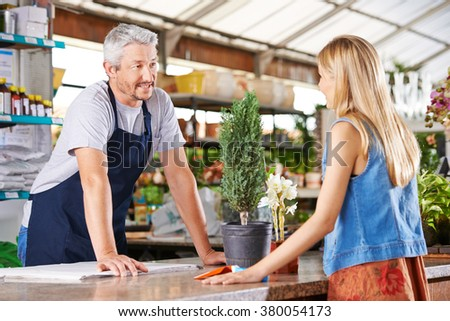 Woman talking with a salesman in nursery shop - stock photo