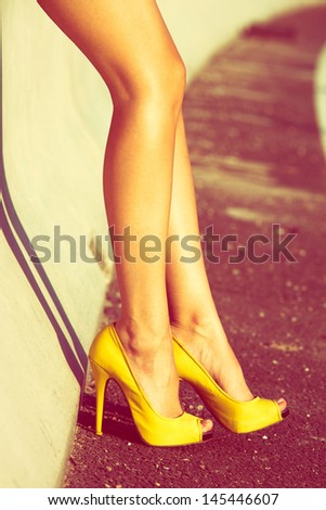 woman tan legs in high heel yellow shoes outdoor shot  summer day - stock photo
