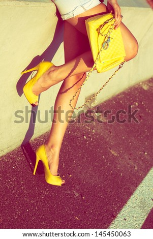 woman  tan legs in yellow high heel shoes and purse on street summer day  - stock photo