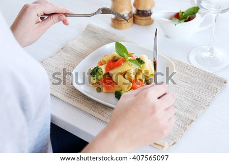 Woman tasting boiled rigatoni pasta with salmon and broccoli at the table - stock photo
