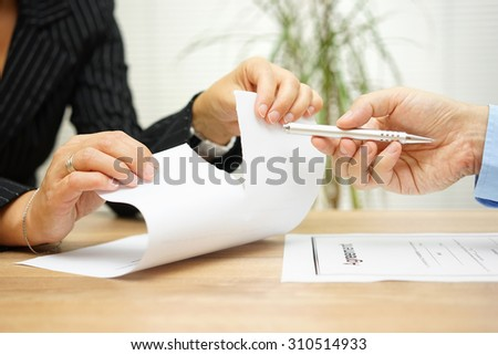 Woman tears agreement documents  in front of agent who wants to get  a signature - stock photo