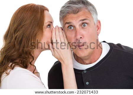 Woman telling secret to her partner on white background - stock photo