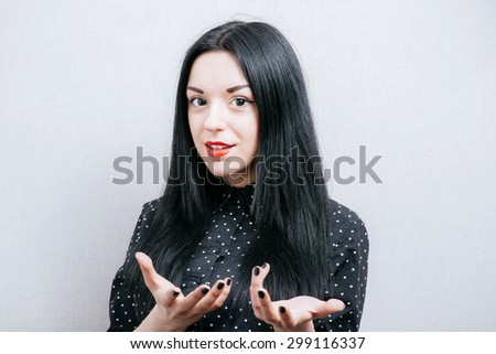 Woman tells showing something with her hands. On a gray background. - stock photo