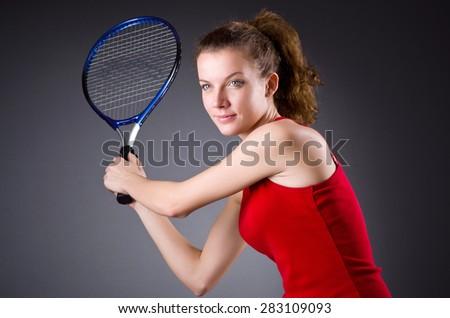 Woman tennis player against dark background - stock photo