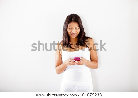 Woman texting on her cell phone - isolated over a white background - stock photo