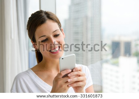 Woman texting on smartphone at home near the window. - stock photo