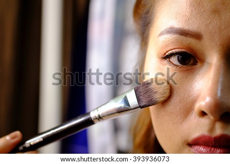 Woman Thailand holding a makeup powder brush to her acne face - No Effect - (Selective focus) - stock photo
