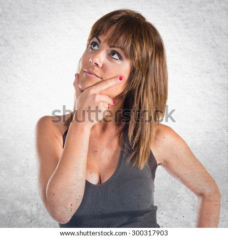Woman thinking and looking up over grey background - stock photo