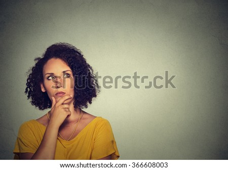 Woman thinking dreaming has many ideas looking up isolated on gray wall background. - stock photo