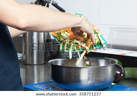 Woman throw some vegetables in a bowl - stock photo