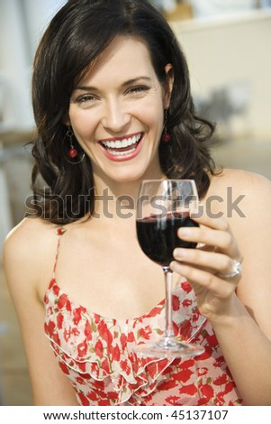 Woman toasts the camera with a glass of red wine. Vertical shot. - stock photo