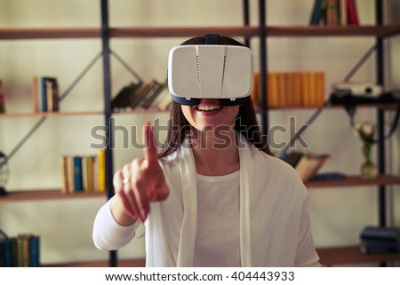 Woman touch something using modern white virtual reality headset glasses - stock photo