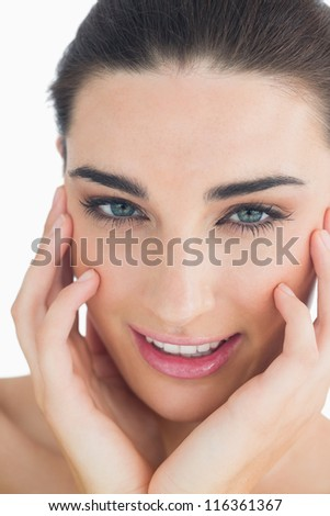 Woman touching her cheek while smiling at camera - stock photo