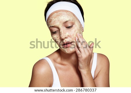 woman touching her face. facial mask. yellow background - stock photo