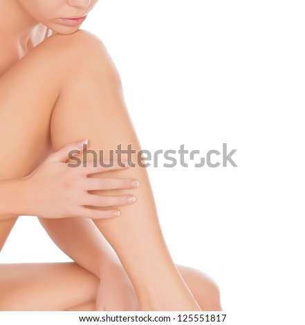 Woman touching her leg, isolated on white - stock photo