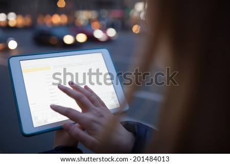 Woman touching tablet screen walking in the street at night - stock photo