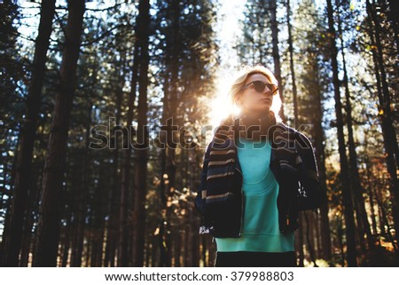 Woman tourist enjoying fresh air while resting after strolling in forest in sunny autumn day, female in trendy sunglasses admires nature while standing near tall trees in the park during fall weekend  - stock photo