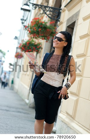 woman tourist holding map and walking in the old town street - stock photo