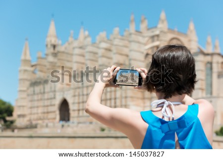 Woman tourist in Mallorca taking photographs of landmark buildings while enjoying the adventure of a a summer vacation in Europe, view from behind - stock photo