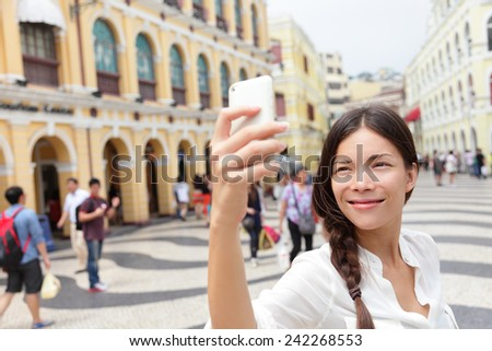 Woman tourist taking selfie pictures in Macau, China in Senado Square or Senate Square. Asian girl tourist using smart phone camera to take photo while traveling in Macau. Travel and tourism concept. - stock photo