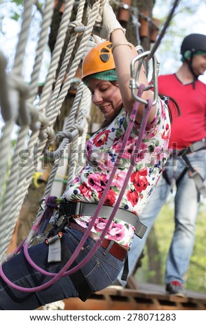 Woman training at Aerial Adventure Park in summer - stock photo