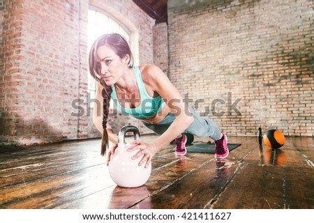 Woman training hard with push up exercise in her gym - stock photo