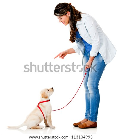 Woman training her dog - isolated over a white background - stock photo