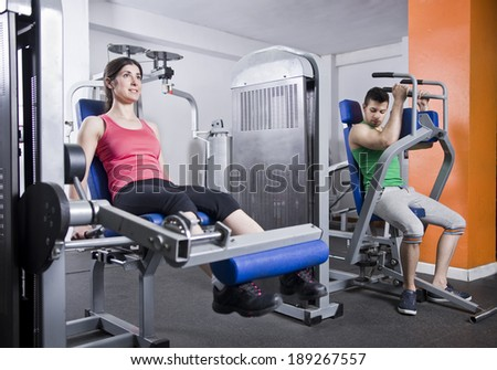 Woman training legs in gym and man training pectoral muscle in background - stock photo