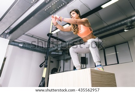 Woman training legs jumping on the cube. Concept about gym and fitness - stock photo