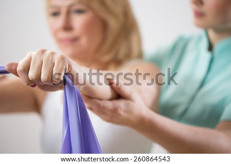 Woman training with exercise band during rehabilitation - stock photo