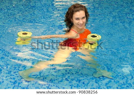 Woman trains in aqua aerobics - stock photo