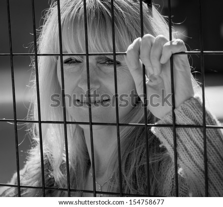 Woman trapped on outside of metal fence looking inside - stock photo