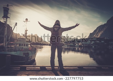 Woman traveler looking at sunset in Reine village with arms wide open - stock photo