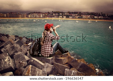 Woman traveler sitting on the stones looking in binocular at horizon. Young female climber with backpack over ocean port background.   - stock photo