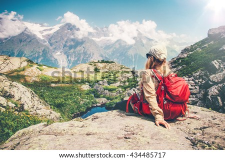 Woman Traveler with backpack relaxing on cliff with mountains landscape on background Travel Lifestyle concept hiking adventure summer vacations  - stock photo