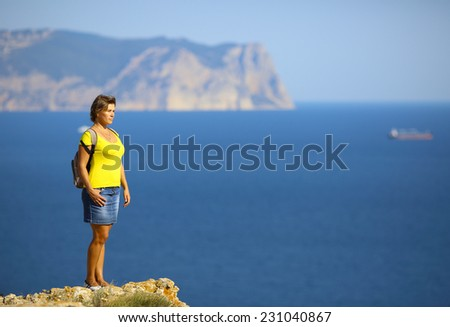 woman traveling on mountain coast - stock photo